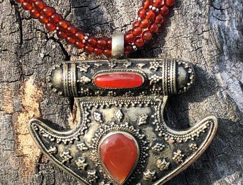 Dieser wunderbare Anhänger aus granuliertem Silber und Karneol wird an einer Kette aus Karneol und Silber getragen.